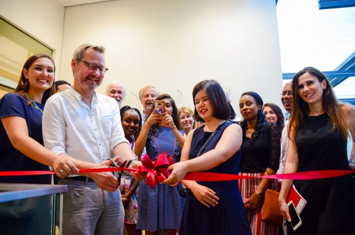 PD Dr. Michael Krennerich of FAU's Human Rights Program cuts the ribbon with the team and the participants to officially open the exhibit at the Erlangen Stadtbibliothek on July 26, 2018.